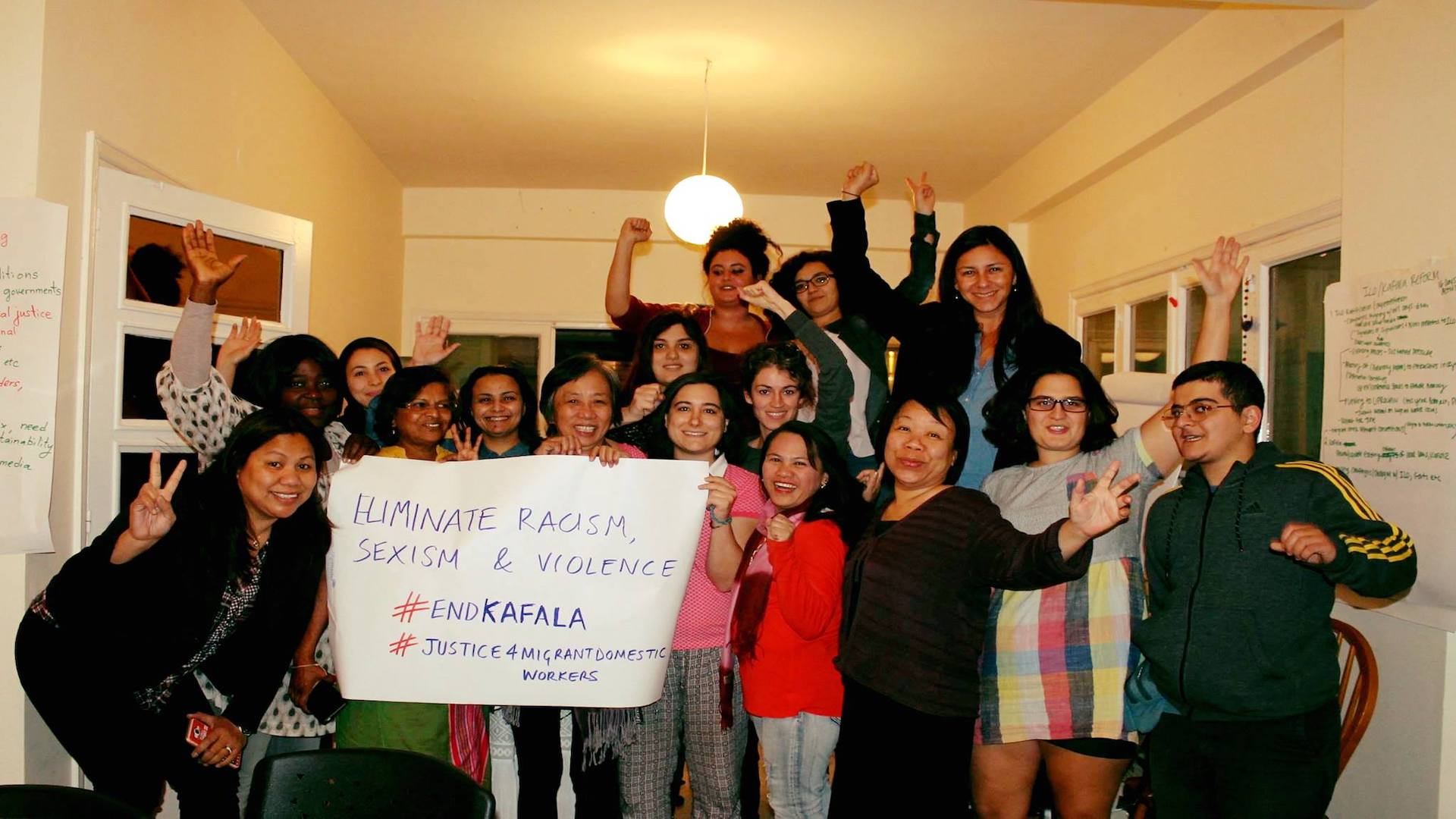 A group of activists holding a sign that says Eliminate racism, sexism and violence and #EndKafala